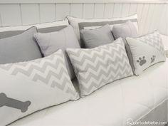 Almofadas da cama de babá com detalhes chevron e estampa de cachorrinhos.