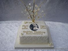 Square 50th golden wedding anniversary cake in ivory colour icing finished with gold coloured text and delicate flower and heart wired gold coloured topper Includes an image of your choice printed in-house edible food colourings