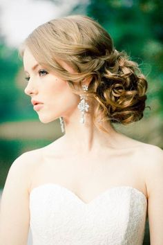 Slightly messy bun to one side paired with statement earrings and perhaps head piece veil?