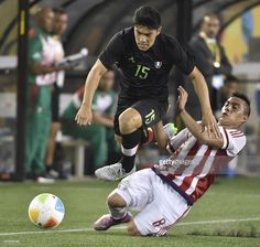 July 13 - Football - Men - First Round.  Paraguay and Mexico tied 1-1.  Angel Lucerna (R) of Paraguay vies for the ball with Michael Perez of Mexico during their group B first round football match against Paraguay of the Pan American Games in Hamilton, Canada, on July 13, 2015. AFP PHOTO / OMAR TORRES