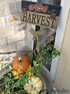 decorating the front porch for fall, design d cor, seasonal holiday d cor, A couple of pumpkins and a harvest yard sign take the potted plant from Summer to Fall