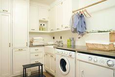 Fantastic laundry room with creamy white shaker cabinets, stainless steel countertops, small farmhouse sink and white washer & dryer