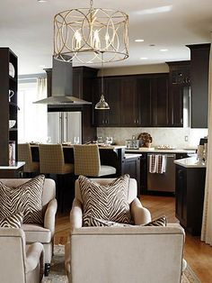 WE JUST BOUGHT THIS LIGHT FIXTURE!!!  :)  Gorgeous chocolate brown kitchen design with espresso kitchen cabinets, cream caesarstone quartz counter tops backsplash, brass chandelier, pendant, chrome yoke island pendants, black white zebra pillows, soft sand beige velvet accent chairs and beige white upholstered counterstools. sand beige chocolate brown black white ivory cream kitchen colors.