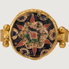 the band is plain, continues under the bezel, cloisonné, 10th century, loops on sides of bezel hook over band.