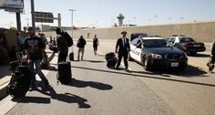 Passengers and airline personnel exit LAX after a Transportation Security Administration agent was shot and killed.