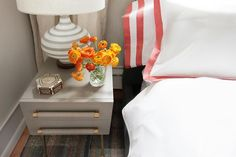 Topped with a white and gray striped lamp, a gray nightstand with gold accents sits beside a bed dressed in red border bedding complemented with red border shams.