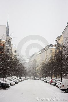 Beautiful winter in Germany. Snowy street with a church and cars.