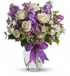 Enchanted Cottage by Bloomers of La Jolla. White roses and spray roses, lavender stock and waxflower, arranged in a clear glass vase with purple ribbon. Starting at $62.95
