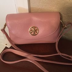 "Tory Burch Robinison mini crossbody in Pink. NWT The perfect ""Go to"" bag to take anywhere with cross body comfort. The pale pink (Rose Sachet) leather is scratch resistant and durable. The leather strap is fully adjustable to be a cross body or shoulder bag. The front flap has the signature T logo with a turn lock closure. Inside there are two compartments and one slot for ID, credit cards, up to an iPhone plus, and one open pocket on the back of the bag. Strap drop measures 23"" on the…"