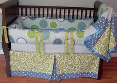 Blue Twister  Included in this set is the bumper, blanket, and crib skirt.  There is a lot of detail in this custom set including soft baby blue minky, grosgrain ribbons, green cartwheel swirl fabric, blue polka dots, and large blue and green circle print.
