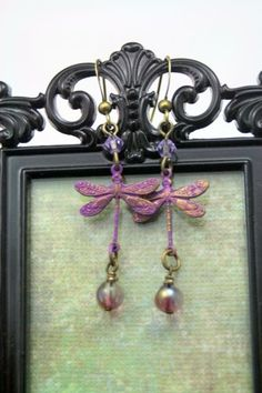 Shades of purple are reflected in these sweet earrings. They are a light weight 2 inches long, with darling dragonflies, painted and buffed back to show off all the details, then accented with a pair