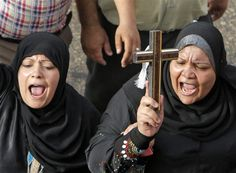 Egyptian Muslim women hold a cross in support of Christians during a memorial march in Cairo for Christians who were killed during deadly clashes with Muslims in April.