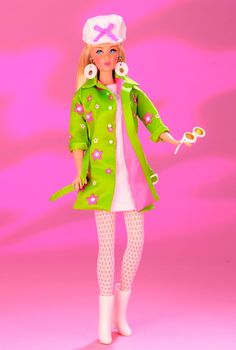 1999 Far Out Barbie ~ It's flower power as Barbie® doll shows off a mod green coat over a white knit dress. With white boots and hat atop her blonde hair, hoop ea...