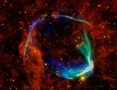 Supernova Remnant RCW 86. Image combines data from 4 different space telescopes to create multi-wavelength view of what remains of oldest documented example of a supernova, RCW 86. Chinese witnessed this in 185AD documenting a 'guest star' that remained in sky for 8 months. Xray images from European Space Agency and NASA Chandra X-ray combine to form blue & green colors in image. X-rays show interstellar gas heated to millions of degrees by passage of shock wave from supernova.