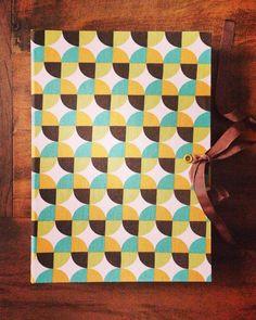Caderno com costura Correntinha, lombada quadrada e capa em tecido de algodão com estampa geométrica.