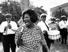 Mahalia Jackson, gospel singer, returned to her hometown to appear at the first New Orleans Jazz & Heritage Festival in April of 1970. While attending the Louisiana Heritage Fair in Congo Square (then known as Beauregard Square), she and Duke Ellington, came upon the Eureka Brass Band leading a crowd of second-line revelers through the Festival grounds. George Wein, producer of the Festival, handed Ms. Jackson a microphone, she sang along with the band and joined the parade.