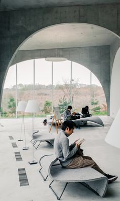 """""""To let the flows and views of these people freely penetrate the building, we began to think of a structure of randomly placed arches which would create the sensation as if the sloping floor and the front garden's scenery were continuing within the building.  """"The characteristic arches are made out of steel plates covered with concrete. In plan these arches are arranged along curved lines which cross at several points.   """"The spatial diversity one experiences when walking through the arches…"""
