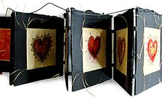'All the Good Souls' by Mia Leijonstedt. Concertina book. This book consists of six pages. There are images of hearts drawn and painted on parchment (leather) which are then stitched with gold thread onto the pages. The pages are sandwiched with a core in the middle to give them a thicker, three-dimensional quality. The pages are attached to each other with leather hinges.