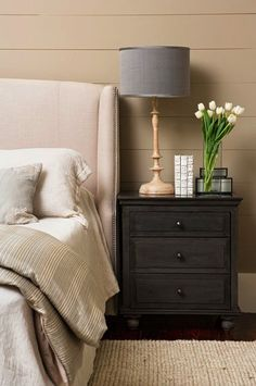 Painted Wood Paneled Walls + Linen Headboard and Lampshade, Black Nightstand, Flowers.