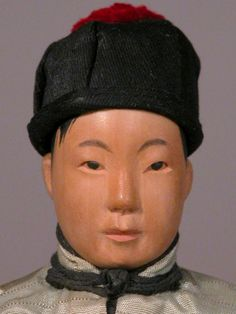 """8.5"""" wooden Door Of Hope boy doll, with western-style hair and silk traditional fashion, China, 1901-49, by N.E. Branch Women's Foreign Missionary Society. Made in Canton, China, these dolls were made by the girls of the Door Of Hope protestant mission home to help destitute children as a fundraising measure, as well as being a representation of local folk art."""
