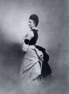1880 was a year between the two bustle eras, but this photo shows fashionable Alexandra's dress has a substantial bustle. Her dress has dark velvet in the bodice, collar around the back of the ruff, elbow pads, and bustle.