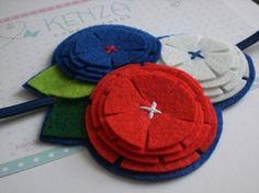 Diadema flor ref:003 - Kenza complementos Diadema con motivos de flores, realizada en fieltro y cinta elástica, de color rojo,blanco y azul El conjunto de flores tiene unos 10 cm de diámetro