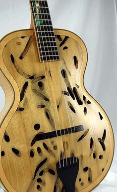 "bigblueguitar:Benedetto Il Teredo II This ultra-rare instrument is the second (and last) featuring matching Teredo-eaten Sitka Spruce tops that Bob Benedetto has fashioned into a museum quality archtop guitar. The first Il Teredo was a more traditional 16″ archtop. This more petite version is 14 1/2″ at the lower bout. Il Teredo II has its own unique appointments: hand applied French polish finish; unique green ""Fredo the Teredo"" Ship Worm, hand cut from reconstituted stone and inlaid to…"