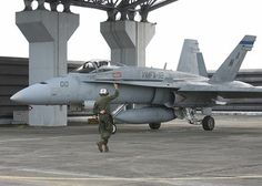 ROYAL MALAYSIAN AIR FORCE BASE BUTTERWORTH, Malaysia - A Marine with Marine Fighter Attack Squadron 112 guides an aircraft along the flightline, Royal Malaysian Air Force Base Butterworth, Malaysia. The Cowboys returned to Iwakuni and are prepareing for their next deployment.