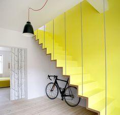 Scala moderna minimal, di colore giallo sole così come la parte superiore del muro. Viene ancorata al soffitto attraverso semplici aste metalliche, creando l'effetto di scala sospesa