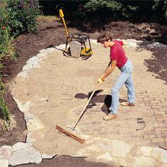 DIY patio using rocks, bricks, and sand ...  Do you love the way he's standing?!
