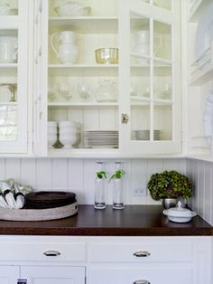 These white kitchen details are divine: white cabinets w/ glass paneled doors, white bead board, dark stained butcher block countertops, old fashioned bin pulls and hardware.   Habitually Chic
