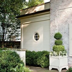 Beautiful side yard with limewash brick, ship lap, round window