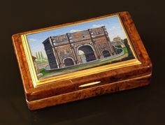 A French 1820's burl wood snuff box with gold lined interior, the hinged cover inset with a Roman micromosaic representing the Arch of Septimius Severus. Excellent condition commensurate with age Dimension cm 8x5x2 the box - cm 6,7x4 the micromosaic The white marble Arch of Septimius Severus (Italian: Arco di Settimio Severo) at the northwest end of the Roman Forum is a triumphal arch dedicated in AD 203 to commemorate the Parthian victories of Emperor Septimius Severus and his two sons.