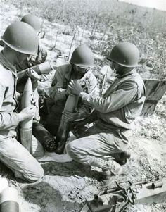 105mm crew preparing the shells during training exercise. Ft. Jackson, 1943. The sergeant in the middle is instructing the soldier on attaching the shell (top part) to the casing below after it has been packed with ammo bags.