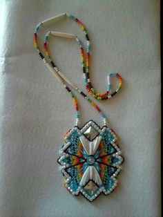 Bead-embroidered medallion with dentalium shells and metal studs.