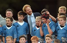 Prince Harry poses for a photograph with a junior team
