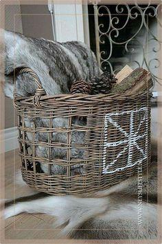 Mooi winters tafereel. Rieten mand gevuld met een bont kussen, dennenappels en houtblokken.