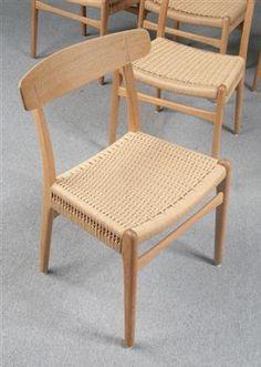 Hans J. Wegner. Fem stole, model CH-23. Stel af massiv egetræ, sæde af flettet papirgarn. Fremstillet hos Carl Hansen & Søn. (5)