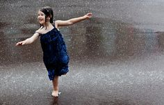 DANCING IN THE RAIN. Taking advantage of a warm rainy day to introduce the children to the joy of movement with the added element of water provides a novel sensory experience, as well as a new awareness of sound elicited  by their many feet moving rapidly through the puddles.