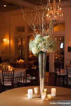 Tall centerpieces are in this wedding season, 2015! Did you know, brides, that your table centerpieces need to be above or below seated guest average eye-level? The nice thing about this centerpiece is that it is a tall vase that your bridesmaids can just place their bouquets into at your reception and then push through a few curly willow branches to change up appearance. That saves you money not having to pay for table arrangements and bridesmaids bouquets.