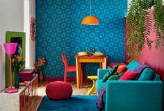 Uma parede azul, outra framboesa. Lustre laranja, sofá turquesa, banquinho amarelo, almofada pink... E não é que essa explosão de matizes co...