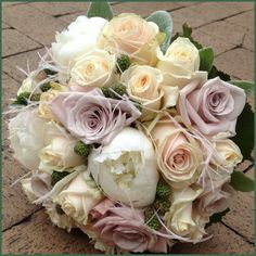 Bouquet for a bride with roses, peonies, blackberries and feathers