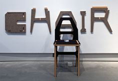 'chair / chair' by eric ku  - as a conceptual example of flat-packed furniture design,   in which wood pieces in the shape of the letters 'c', 'h', 'a', 'i', and 'r' are assembled into a seating unit.   'instead of giving new definition [to the object],' he explains, 'I redefined the concept of a chair by using   the alphabet. one is able to construct a chair by assembling the redesigned letters.
