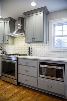 Brite White Subway Tile 3x6, Classic French Gray Shaker Cabinets, MSI Carrara Grigio Quartz, Blanco Sonoma Anthracite faucet, Blanco Precis Cascade Super Single Bowl Cinder, Floating Shelves, Range: JennAir JDS1450DS, Hood: Broan RME5030SS, Fridge: LG LFX25991ST/02, Dishwasher: LG LD7774ST, Wine Cooler: NewAir AW-321ed, Industrial Elements Wall Sconce, microwave LCRT2010ST Wall color SW9166 Drift of Mist