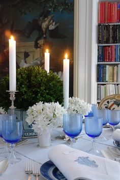 boxwood in blue and white bowl. Mint julep cuts with white flowers...and blue goblets, on a white cloth, blue and white plates, silver candlesticks...very lovely and unusual for Christmas