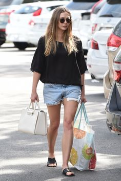 Elizabeth Olsen was recently spotted shopping in LA wearing the perfect distressed duo, pairing a cut-off sleeve sweater with denim cut-offs. She finished the look with some round sunglasses, a white tote bag, and leather slide sandals.