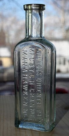 Nichols Oriental Balm - aqua, tooled square lip, rectangular, 4 15/16in (126mm) tall. No vent hole bumps. Embossing: NICHOLS ORIENTAL BALM / MFG. BY C.H. CRANMER / MANAHAWKEN, N.J. (up back) - c1880. Old Medicine Bottles, Old Glass Bottles, Antique Bottles, Vintage Bottles, Bottles And Jars, Glass Photo, Bottle Art, Sea Glass Jewelry, Tins