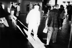 Photo by Trent Parke. The lighting in this is great, with the man highlighted by the Ray of light looking ghostly due to over exposure, I like the contrast. The black and white makes the subject stand out. Love the long shadow in the strip of light