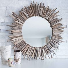 A beautiful rustic round mirror framed by pieces of driftwood. Sstep-by-step tutorial for this coastal, beach-inspired DIY home decor idea.