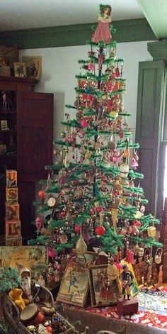 Antique Decorated Green Feather Tree ,with antique toys around it.
